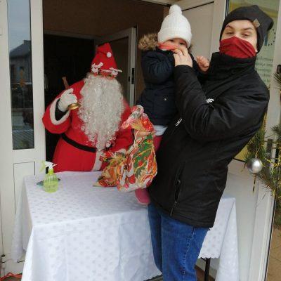 Św. Mikołaj wręcza paczkę dziecku z Mierzowic