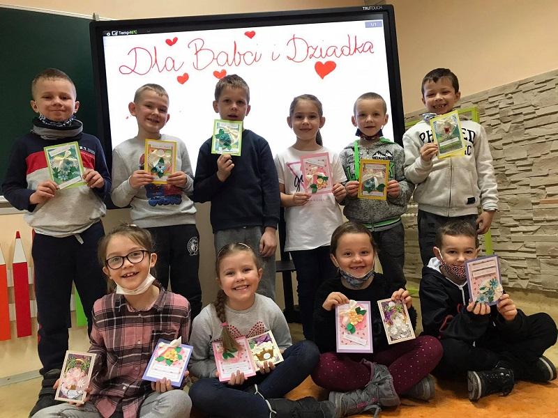 Uczniowie z edukacji wczesnoszkolnej z własnoręcznie przygotowanymi kartki z życzeniami